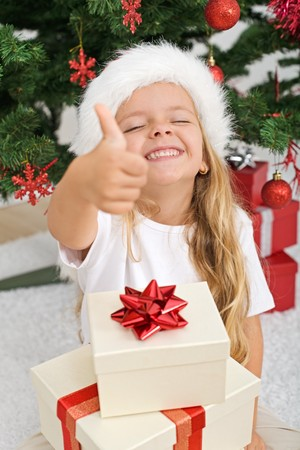 allright: Extremely happy litte girl with thumbs up holding lots of christmas presents Stock Photo