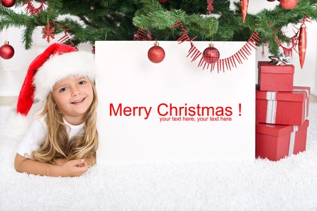 Little girl laying under the christmas tree with banner for text photo