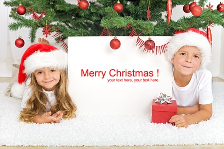 children celebration: Happy kids laying under the christmas tree with a white banner for text Stock Photo
