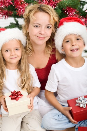 Woman and kids with presents at christmas time - tired but happy photo