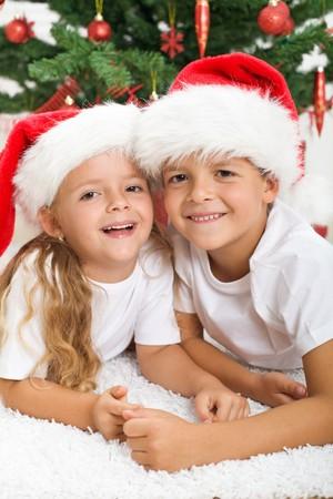 joyfully: Happy kids in front of christmas tree laughing joyfully