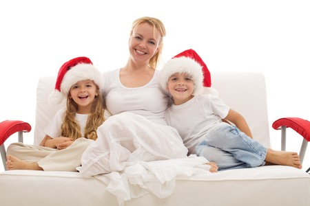 Happy woman and kids sitting on a sofa wearing christmas hats - isolated Stock Photo - 8114384