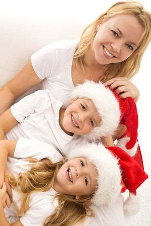 Happy kids and woman relaxing on the white sofa at christmas time - closeup photo