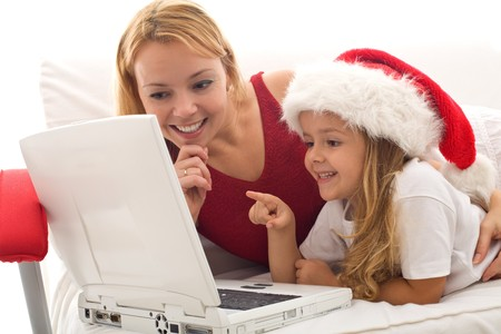 Woman and little girl playing on a laptop at christmas time - online shopping for holidays concept photo