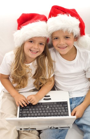 Searching for the perfect christmas gift online - kids with laptops and santa hats Stock Photo - 8114456