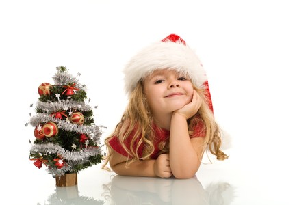 Little girl with small christmas tree on the table dreaming about the holidays - isolated, copuy space Stock Photo