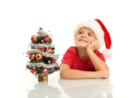 Boy dreaming of christmas by a small decorated tree - isolated Stock Photo - 8114347