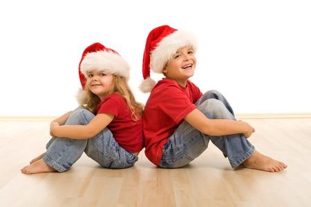 piedi nudi ragazzo: Bambini felici sul pavimento indossare cappelli di Natale, ridendo e avendo divertimento - isolato
