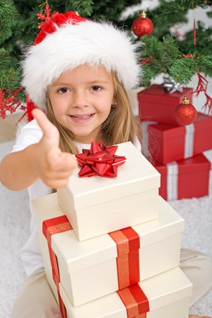 Happy little girl with lots of christmas presents giving the thumbs up sign Stock Photo - 8344606
