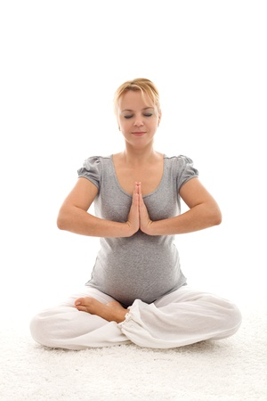 prenatal care: Pregnant woman doing exercises sitting peacefully on the floor - isolated