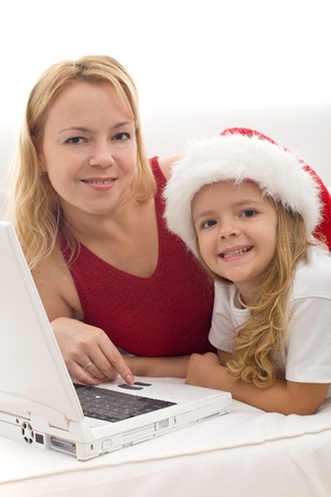 Woman and little girl searching for christmas presents on the internet using a laptop Stock Photo - 8344599