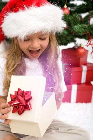 Excited little girl opening christmas present with magical glow in front of the fir tree - closeup photo
