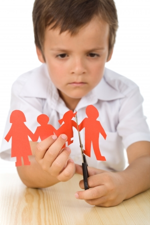 divorce: Sad boy cutting paper people family - divorce effect on kids concept, isolated closeup