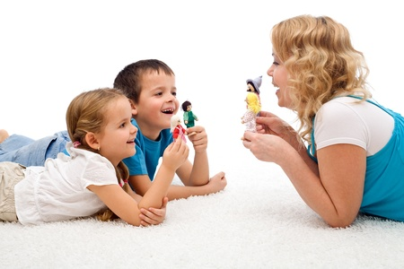 Happy woman and kids playing on the floor with puppets - isolated photo