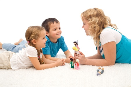 toy story: Woman telling a story to her happy kids laying on the floor and illustrating it with puppets - isolated