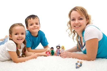 Happy woman and kids playing on the floor with puppets smiling - isolated Stock Photo