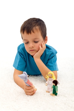 Divorce effect on kids  concept with thoughtful boy playing with puppets on the floor - isolated photo