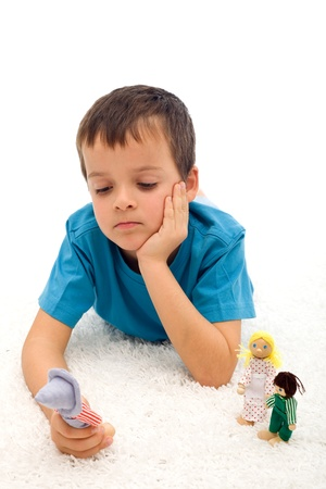Sad boy thinking of his separated family playing with figurines on the floor - divorce concept, isolated photo
