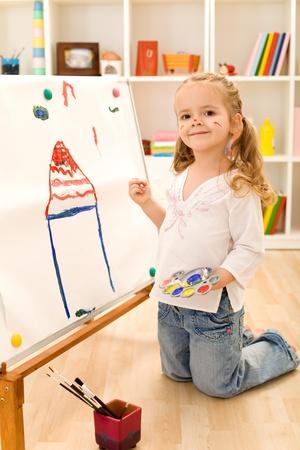 droomhuis: Lachende kunstenaar meisje haar droomhuis op een grote papieren doek schilderij