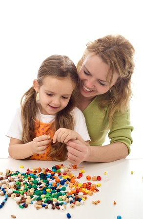 a beads: Woman and little making a necklace from wooden beads and a string - isolated Stock Photo