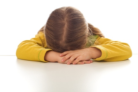 sulking: Little sad girl sulking or crying at the table - isolated Stock Photo