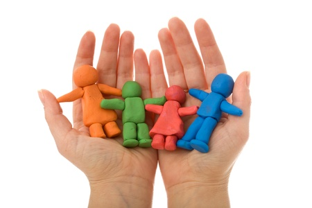 protect family: Woman hands holding colorful clay people - united happy family concept, isolated