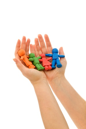 Hands holding colorful clay people - caring family concept, isolated photo