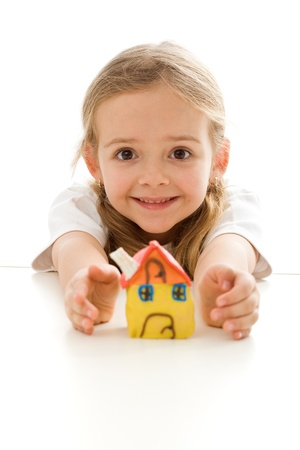 Ecstatic little girl with her clay house grimacing happily - isolated Stock Photo - 9182935