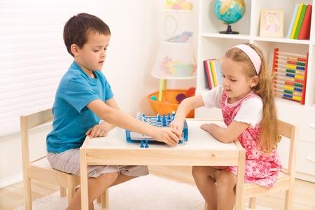 jugando ajedrez: Hermanos jugar al ajedrez en su habitaci�n sentado a la mesa Foto de archivo