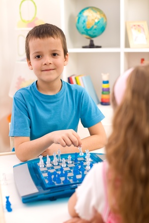Kids playing chess sitting at the table in their room Stock Photo - 9182933