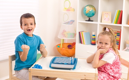 rivalry: Childhood rivalry among siblings - boy winning chess game, his sister upset Stock Photo