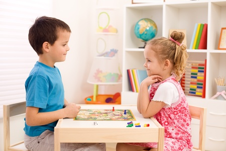 little table: Little boy and girl playing board game in their room sitting at the table Stock Photo