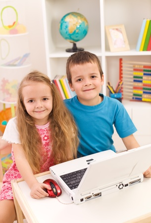 Little boy and girl with laptop computer in their room smiling to the camera photo
