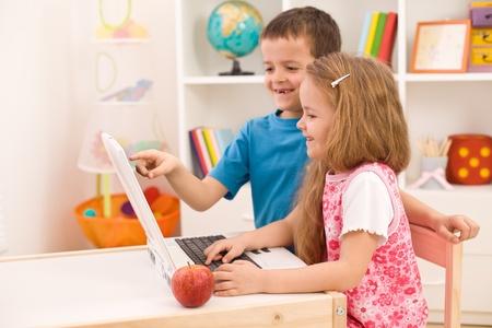 deberes: Ni�os jugando juntos en el equipo port�til en casa