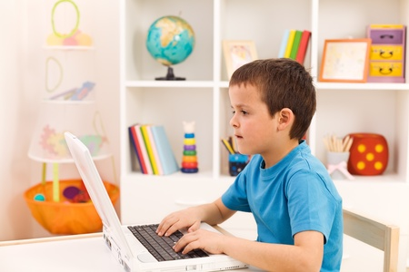 Boy playing or working on laptop computer in his room Stock Photo - 9187318