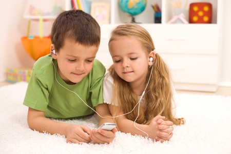 Little boy and girl listening to music together on a portable player, laying on the floor photo
