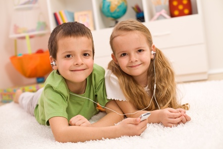 Little boy and girl listening to music together sharing earphones, laying on the floor at home photo