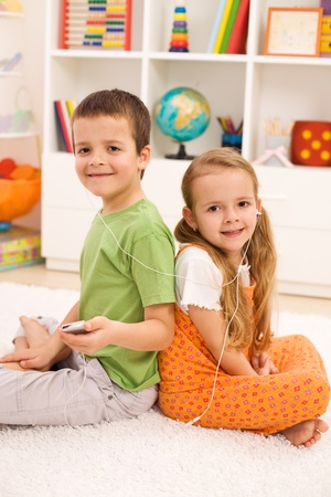 Modern casual kids listening to music in their room sitting on the floor photo