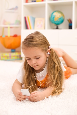 Little girl listening to music laying on the floor in her room using earphones photo