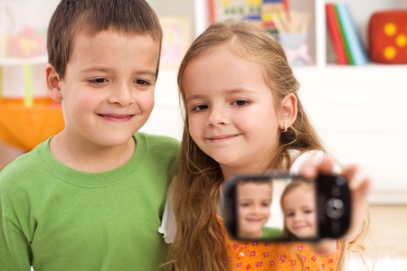 self communication: Kids taking a photo of themselves using a modern mobile phone