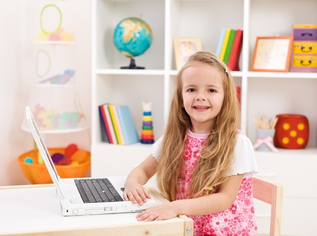 Happy little girl in her room working on laptop computer smiling photo