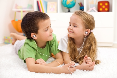 Kids sharing earphones listening to music laying on the floor