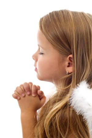 personas orando: Adorable ni�a rezando pac�ficamente - aislado, detalle Foto de archivo