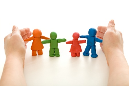 Hands protecting colorful clay people family - on white Stock Photo - 9824188