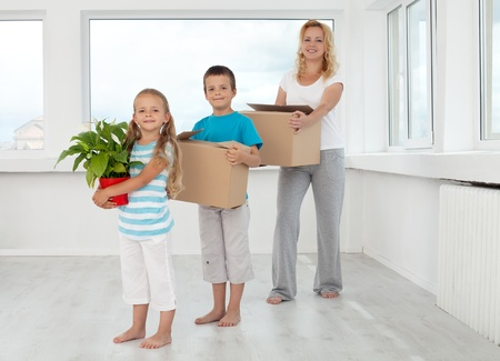 Family moving into a new home carrying cardboard boxes and plants photo