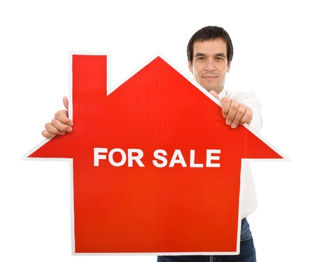 Confident salesman holding house for sale sign - isolated photo