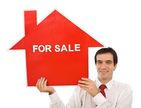 Salesman smiling holding house for sale sign - isolated photo