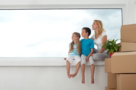 Happy people looking out the window of their new home with cardboard boxes and lots of copyspace photo