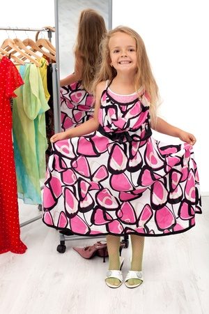 przewymiarowany: Little girl having fun trying mothers clothes in front of mirror