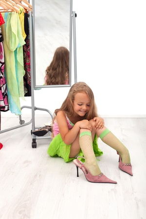 Little girl  sitting on the floor trying on high heel shoes photo